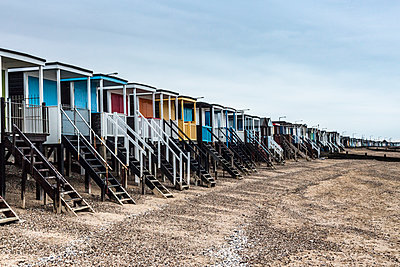 Multicolored changing cubicles on the beach - p1130m1119530 by Jonathan Kitchen