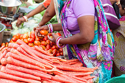 Indian women in traditional Sarees at food market buying vegetables - p1166m2096179 by Cavan Images
