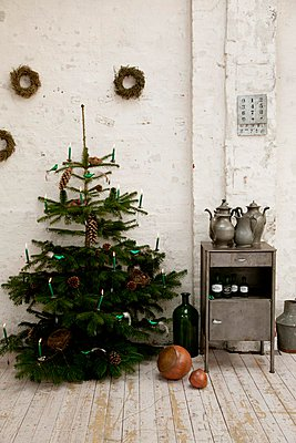 Christmas tree with lit candles next to small vintage cabinet against white wall in rustic atmosphere - p1183m996979 by Grossmann.Schuerle