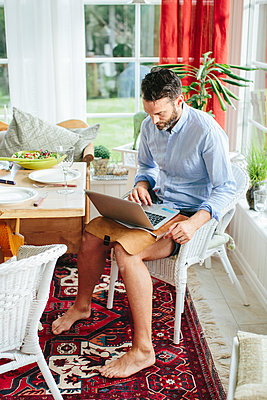 Man using laptop - p312m1180360 by Anna Rostrom