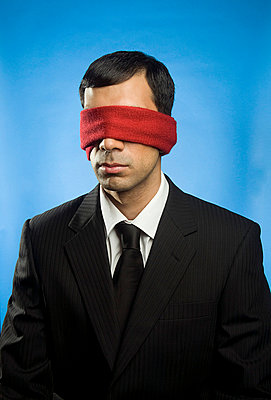 Man blindfolded with red scarf - p5120082 by Emma Innocenti
