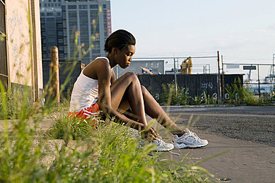 Runner sitting on sidewalk - p9245273f by Image Source