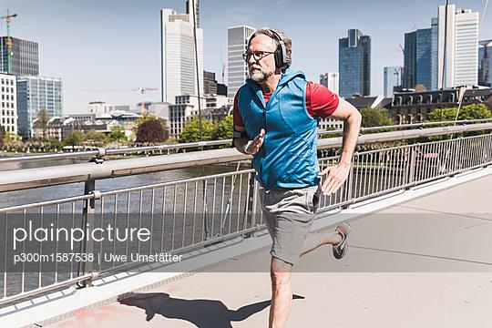Mature man with headphones running on bridge in the city - p300m1587538 von Uwe Umstätter