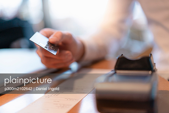 Customer paying bill with credit card, close-up - p300m2102642 von Daniel Ingold
