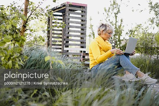 Mature woman sitting on bench outdoors using laptop - p300m2121278 by Kniel Synnatzschke