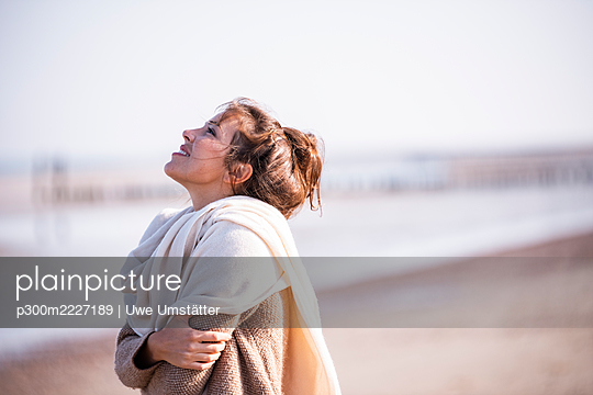 Smiling woman with arms crossed looking up at beach on sunny day - p300m2227189 by Uwe Umstätter
