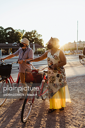 Senior couple with bicycle standing at roadside on sunny day - p426m2239074 by Maskot