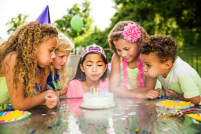 Girl blowing birthday cake candles while standing with friends in backyard - p1166m1096837f by Cavan Images