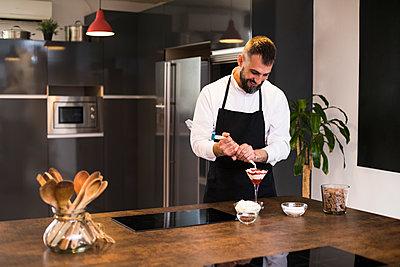 Smiling chef making dessert in kitchen - p1166m2124228 by Cavan Images