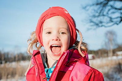 portrait of young girl laughing whilst playing outside in winter - p1166m2159459 by Cavan Images