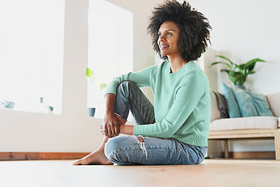 Young thoughtful woman looking away while sitting on floor at home - p300m2276456 by Steve Brookland