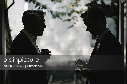 Silhouette of two businessmen drinking coffee together - p300m2202672 by Gustafsson