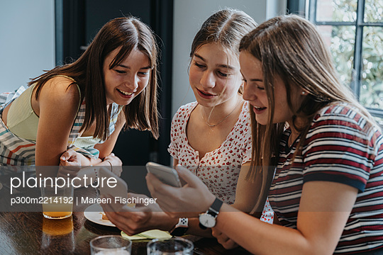 Group of teenage girls meeting for brunch, looking at smartphones - p300m2214192 by Mareen Fischinger
