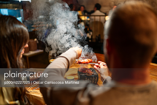Man holding food while sitting by table at restaurant - p300m2227025 by Oscar Carrascosa Martinez