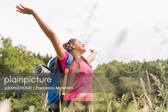 Female backpacker with arms outstretched standing in meadow - p300m2290531 by Francesco Morandini