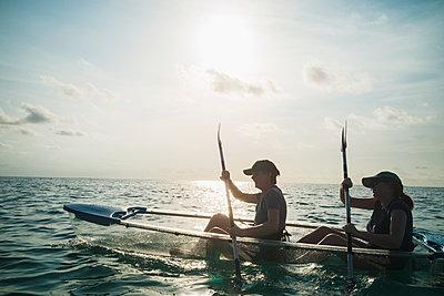 Women in clear bottom canoe on sunny ocean, Maldives, Indian Ocean - p1023m2024457 by Martin Barraud