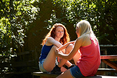 Preteen girl friends talking on sunny picnic bench in summer backyard - p1023m2238507 by Himalayan Pics