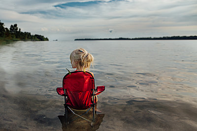 Little girl sitting in chair at beach on a summer day - p1166m2189640 by Cavan Images
