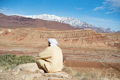Morocco, Man with turban looking at the Atlas Mountains - p1167m2269979 by Maria Schiffer