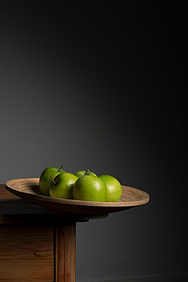 Five green apples in wooden bowl balanced precariously on the edge of a table. - p1433m1586553 by Wolf Kettler