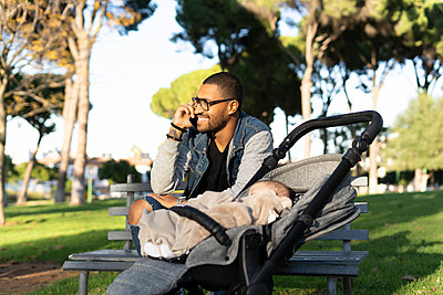 Working father in a park,  talking on the phone, with baby in pram - p300m2154757 by Eloisa Ramos