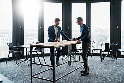 Smiling male business people talking at table in office cafe - p300m2273902 by Daniel Ingold