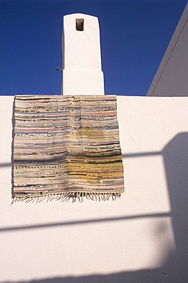 Rug hanging over a white wall of a private house in Greece - p3313571 by Andrea Alborno