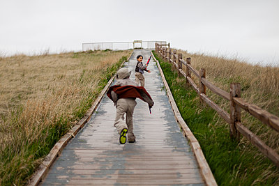 Boys running on wooden path - p343m1446667 by Steve Glass
