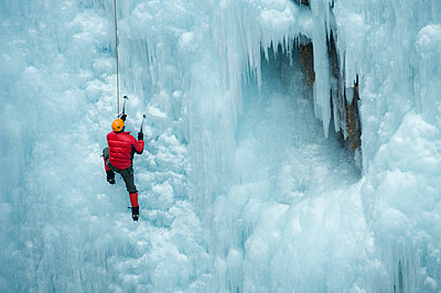 Caucasian man climbing ice wall - p555m1479337 by Pete Saloutos