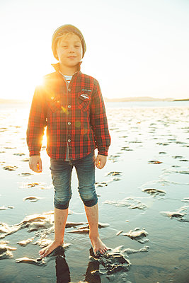 Boy with cap on the beach at low tide, California - p756m2211791 by Bénédicte Lassalle