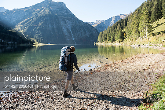 Junger Mann wandert an Bergsee - p1142m2056461 von Runar Lind