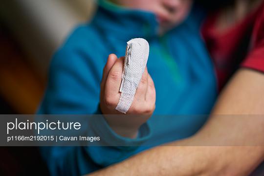 Crop child showing bandaged finger - p1166m2192015 by Cavan Images