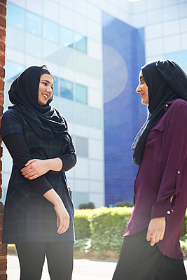 Young women friends in hijabs talking outside sunny building - p1023m2161778 by Himalayan Pics