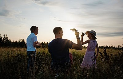 father playing with paper aeroplanes with son and daughter at sunset - p1166m2137838 by Cavan Images