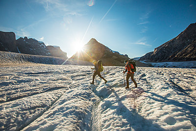 Two hikers crossing a large glacier in Auyuittuq National Park - p1166m2205808 by Cavan Images