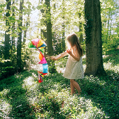 Mädchen im Wald spielt mit einem Drachen - p1270m1105833 von Annabel Sougne