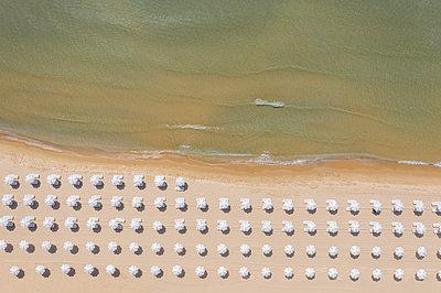 Aerial view to a beach umbrellas on the coast of sea resort - p1596m2192876 by Nikola Spasov