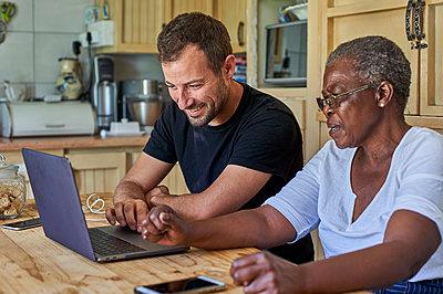 Senior woman and smiling man sitting at kitchen table sharing laptop - p300m2155900 von Veam