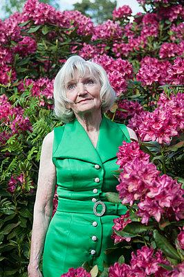 Dame in grün vor Rhododendron - p310m1069582 von Astrid Doerenbruch