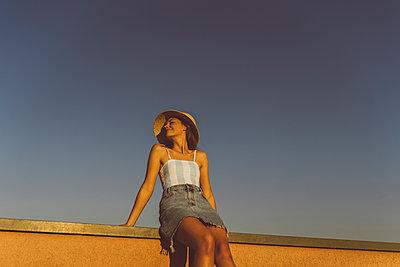 Junge Frau mit Hut entspannt auf Hausdach - p432m2260446 von mia takahara