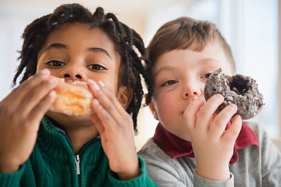 Close up of boys eating donuts - p555m1410965 by JGI/Jamie Grill