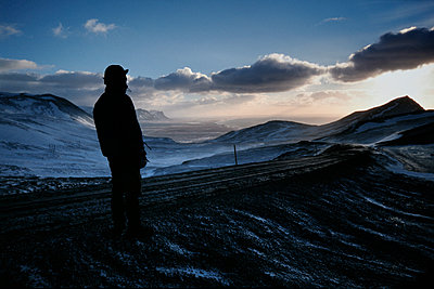 Man looking far away, Route 54, Snaefellsnes peninsula with sea in distance, Iceland - p1028m2045334 von Jean Marmeisse