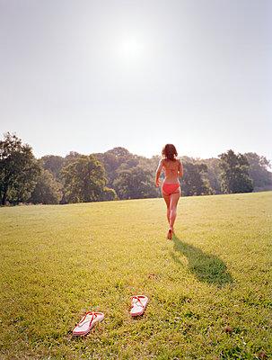 Woman in bikini running over meadow - p1207m1111689 by Michael Heissner