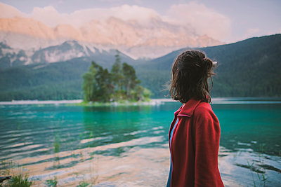 Germany, Bavaria, Eibsee, Young woman standing at byÊEibseeÊlake in Bavarian Alps and looking at view - p1427m2174058 by Oleksii Karamanov