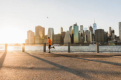 USA, Brooklyn, man jogging in front of Manhattan skyline in the evening - p300m1205514 by Uwe Umstätter