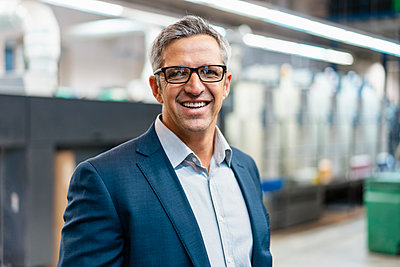 Portrait of a smiling businessman with glasses in a factory - p300m2160252 by Daniel Ingold