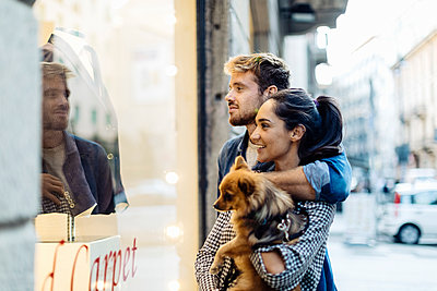 Young couple with dog looking in shop window in the city - p300m2170759 by Sofie Delauw