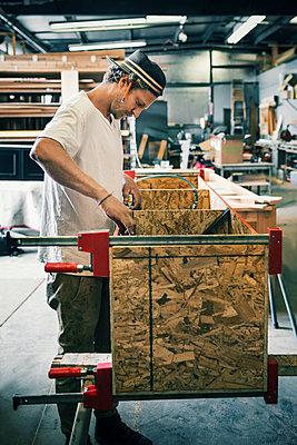 Side view of carpenter making furniture at workshop - p426m1062628f by Maskot