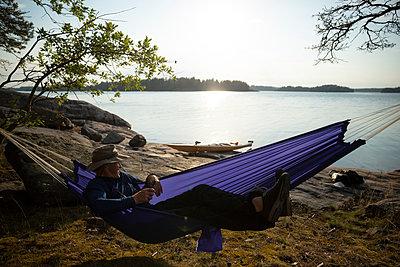 Smiling man enjoying on hammock by lake during summer - p426m2217774 by Katja Kircher