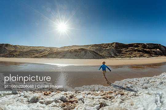 View from ocean of young child running from waves on a sunny day in New Zealand - p1166m2208046 by Cavan Images
